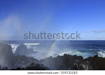 Wave splash with rainbow on the rocks, Azores, Portugal - stock photo