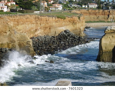 Wave splashing against the rocks. - stock photo