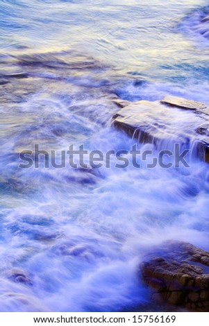 Wave washing on Boiling Pot Rocks, Noosa, Queensland, Australia, using a long exposure to blur water. - stock photo