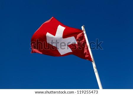 Waved Switzerland National Flag on the sky background - stock photo