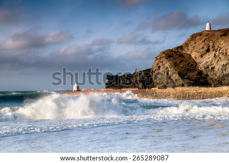 Waves and surf at Portreath harbour on the coast of Cornwall, the structure on the pier is known as the Monkey Hut and the one on the cliffs the Pepperpot - stock photo