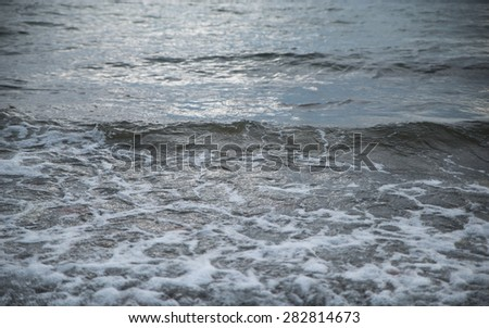 Waves at the seashore. Selective focus with shallow depth of field. - stock photo