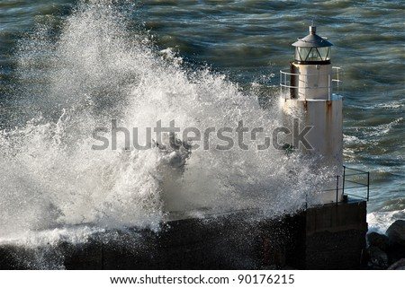 Waves breaking against a lighthouse in Italy - stock photo