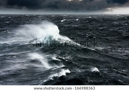Waves Breaking and Spraying at High Seas and Strong Winds - stock photo