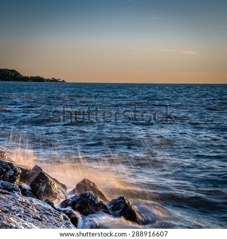 Waves breaking on rocky shoreline in Wisconsin on Lake Michigan at sunrise - stock photo