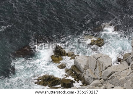 Waves breaking on the rocks . The waves rolled ashore and breaking on the rocks . - stock photo