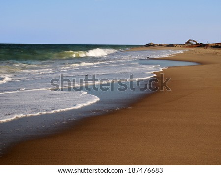 Waves breaking on the shore of a beach that is being restored with a bulldozer in the background. - stock photo