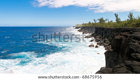Waves breaking on volcanic cliffs of Reunion island with blue sky and cloudscape background. - stock photo