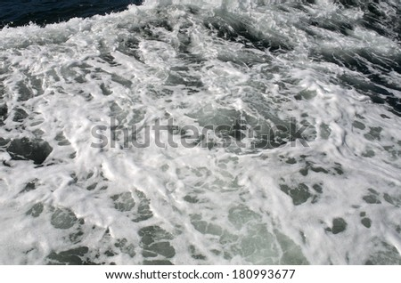 Waves caused by boat while traveling in the ocean - stock photo