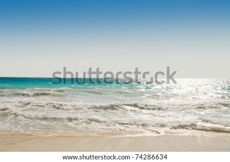 Waves coming onto a beach on a sunny day - stock photo