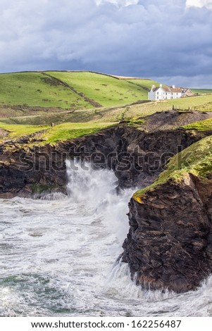 Waves Crash Against North Cornwall Cliffs - stock photo