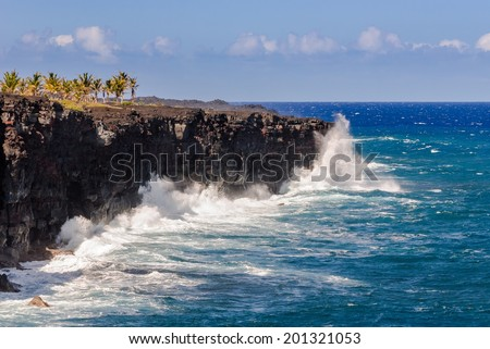 Waves crash into an old lava bench at Hawaii Volcanoes National Park on the Big Island of Hawaii.  - stock photo