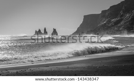 Waves crash into the rocky black beaches near Vik, Iceland. - stock photo