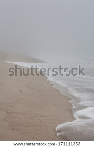 Waves crash on a Cape Cod beach during a foggy morning. Waves and wind, in association with sea level rise, are eroding many coastlines throughout the east coast and the world. - stock photo