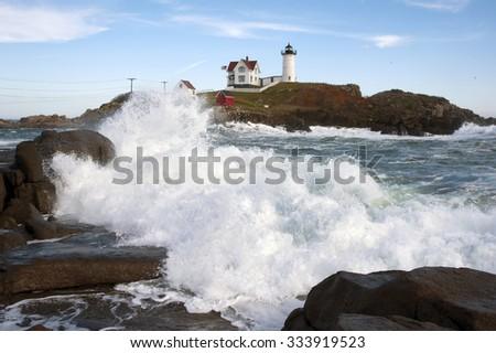 Waves crashing along the shoreline near Nubble (Cape Neddick) lighthouse in Maine. - stock photo