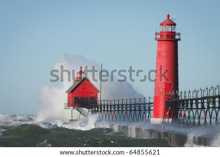 Waves crashing on lighthouse. Grand Haven lighthouse on Lake Michigan. Horizontal format. - stock photo