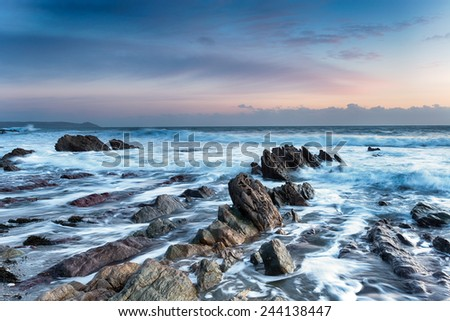 Waves crashing on rocks at Finnygook beach at Portwrinkle in Cornwall - stock photo