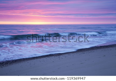 Waves crashing on the beach at dawn . - stock photo