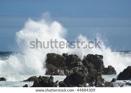 Waves crashing violently on big rocks making huge splashes, with blue skies above and behind - stock photo