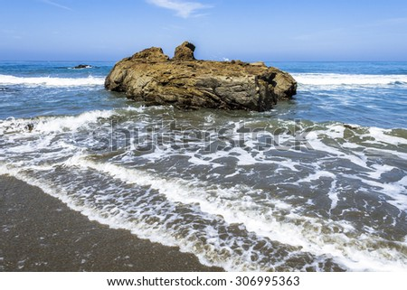 Waves crushing / breaking on a sandy/ rocky beach making sea foam along the rugged Big Sur coastline, near Cambria, CA. on the California Central Coast. - stock photo