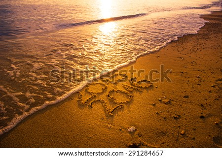 Waves erase old 2015 year on the beach at sunset - stock photo
