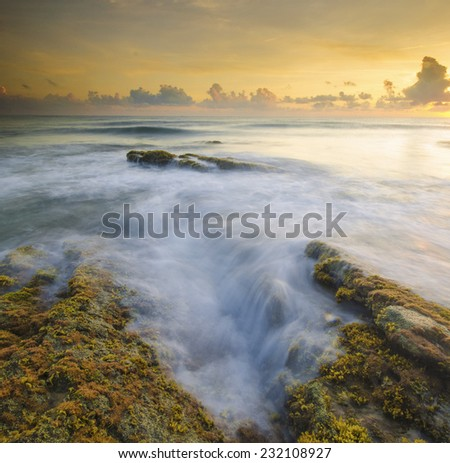 Waves Flow Hit the Rock During Sunrise. A little noise grainy texture. - stock photo