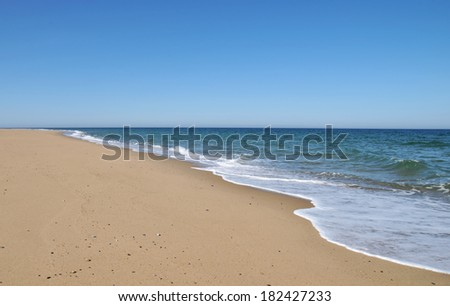 Waves from the receding tide lap the sand at Race Beach on Cape Cod - stock photo