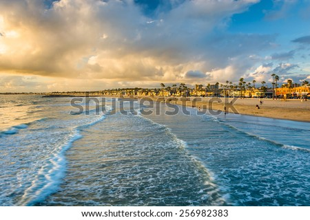 Waves in the Pacific Ocean and view of the beach at sunset, in Newport Beach, California - stock photo