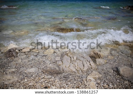 Waves lapping over a rocky shore on Flowerpot island - stock photo