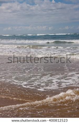 waves lapping sandy shore at surf beach, Gisborne, New Zealand  - stock photo