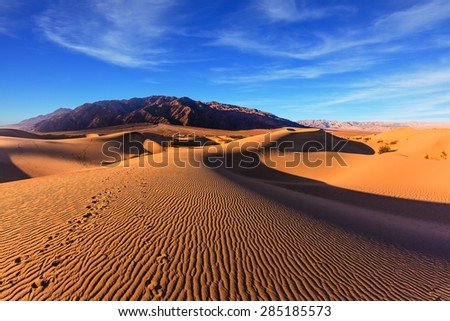 Waves of orange sand on top of the dunes. Sunrise. Desert in Mesquite Flat, Death Valley, USA. The photo was taken Fisheye lens - stock photo