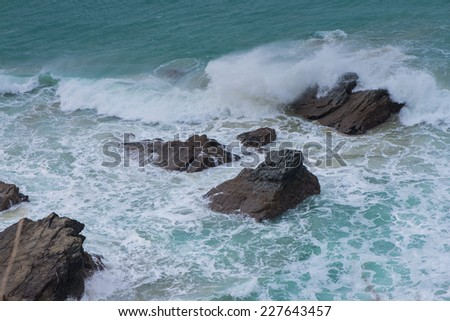 waves on cornish rocky cliff in Newquay - stock photo