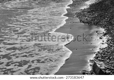 Waves on stone beach waters edge abstract sea background. Black and white. - stock photo