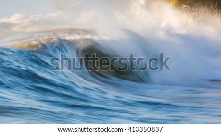 Waves on the ocean captured with a slow shutter speed to bring a sense of movement and power. - stock photo