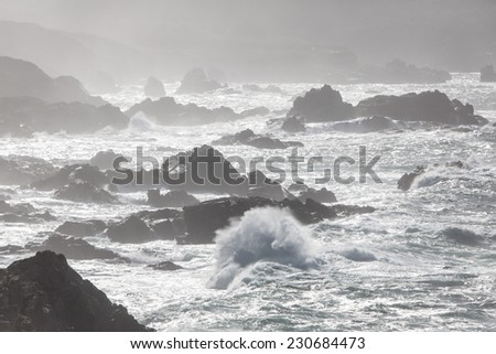 Waves pound against the rocky coast of Big Sur in northern California. The natural scenery along this part of the Pacific shoreline is incredibly beautiful and dramatic. - stock photo