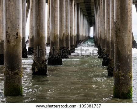 Waves roll in below an ocean pier. - stock photo