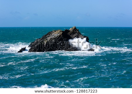 Waves smash into an offshore rock - stock photo