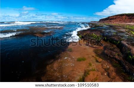 Waves splash against rocks and red sand on PEI Coast - stock photo