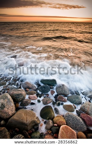 Waves wash ashore during a beautiful sunset. Taken at Gros Morne national park in Canada, which is a UNESCO world heritage site. - stock photo