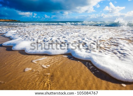 Waves wash over golden sand on Australian beach - stock photo
