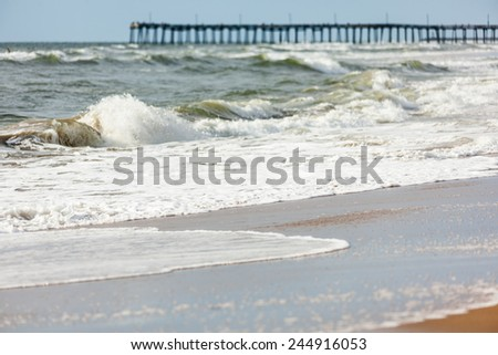Waves washing on shore at the pier on Virginia Beach - stock photo