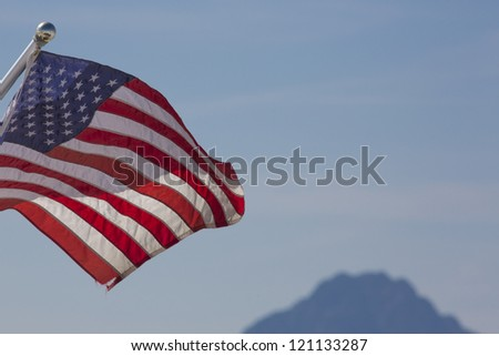 Waving American flag against cloudy blurred sky in the background. - stock photo