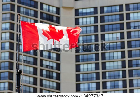 Waving canadian flag and building in the background - stock photo