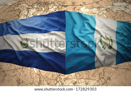 Waving El Salvador and Guatemalan flags on the of the political map of the world - stock photo