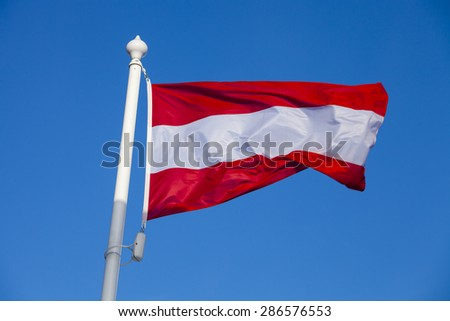Waving flag of Austria against the blue sky - stock photo