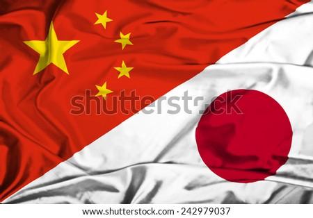 Waving flag of Japan and China - stock photo