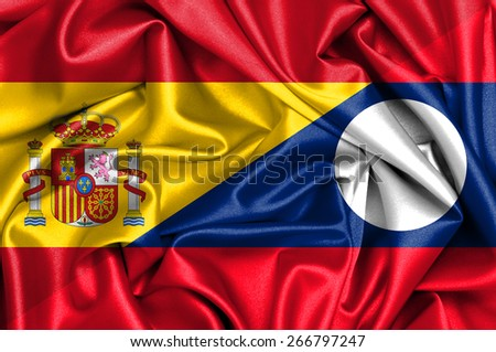 Waving flag of Laos and Spain - stock photo
