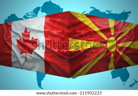 Waving Macedonian and Canadian flags of the political map of the world - stock photo