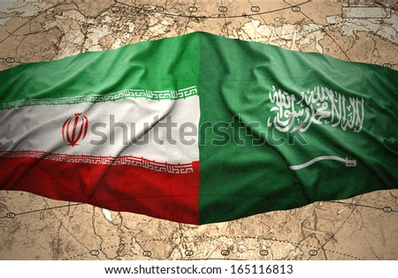 Waving Saudi Arabia and Iranian flags on the background of the political map of the world - stock photo