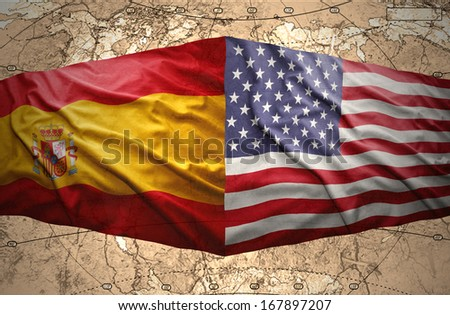 Waving Spanish and United States of America flags on the background of the political map of the world - stock photo